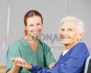 Alte Frau mit Krankenpflegerin im Pflegeheim