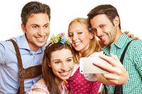 Gruppe in Bayern macht Selfie mit Smartphone