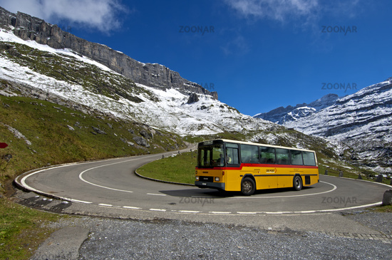 Yellow Swiss Post bus in a hairpin bend