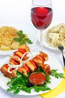 table with food of meat on skewer, dumplings and gass of red wine.