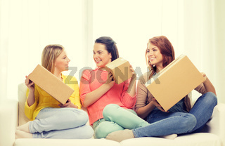 smiling teenage girls with cardboard boxes at home