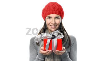 Hübsche Frau in Winterkleidung hält ein Geschenk