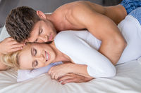 Romantic Couple Lying on White Bed