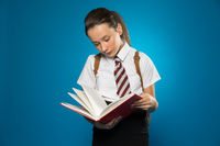 Young schoolgirl reading from a class text book