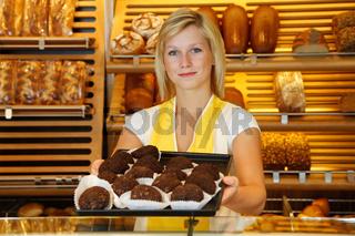 Shopkeeper in bakery presents tablet of rum balls