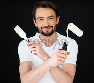 Smiling painter holding a roller and brush