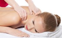 Beautiful caucasian woman lying on the massage table and is being massaged.