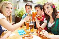 Frauen stoßen mit Bier an im Biergarten