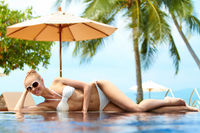 Blond woman sunbathing on an infinity pool