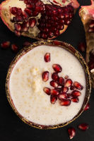 Dish of banana millet breakfast pudding with pomegranate