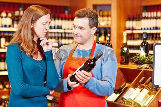 Verkäufer gibt Frau Beratung beim Kauf von Wein
