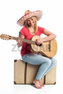 eine frau sitzt auf einem koffer und spielt gitarr