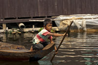 Boy paddling in a boat on the Tonle Sap lake