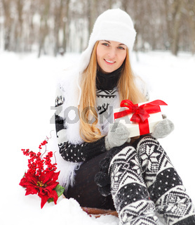 Young smiling woman holding gift decorated with red ribbon