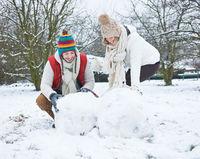 Paar baut einen Schneemann im Winter