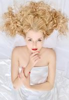Beautiful woman with curly  hair and red lips  laying on white linen.