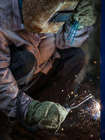 Arc welder worker in protective mask welding metal