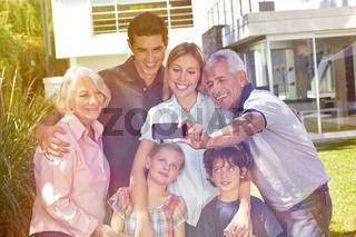 Familie macht Selfie mit Smartphone im Garten
