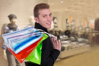 Lachender junger Mann beim Einkaufen mit Taschen in einem Geschäft
