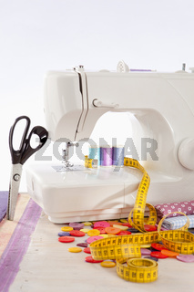 Sewing machine with many sewing utensils on a wooden box