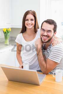 Young couple smiling at the camera using laptop