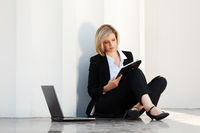 Young business woman with laptop at the wall