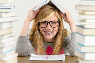 Smiling student teenager holding book over head