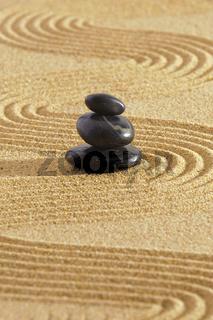Japanese zen garden with stacked stones in sand