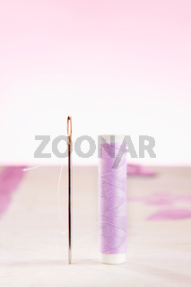 Standing sewing needle with purple thread