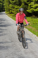 Woman riding bike on sunny cycling path