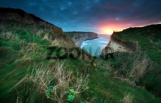 sunset over cliffs in ocean