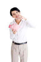Businesswoman putting a coin into a piggy bank