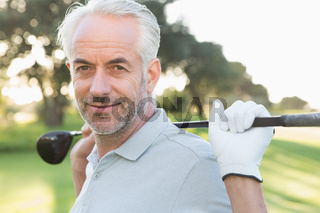 Smiling handsome golfer looking at camera