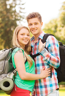 smiling couple with backpacks in nature