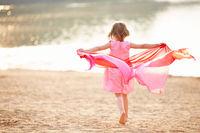 Mädchen mit Tuch läuft am Strand