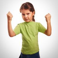 Angry evil girl shows fists experiencing anger and emotion