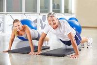 Frau und Mann machen Liegestütze im Fitnesscenter