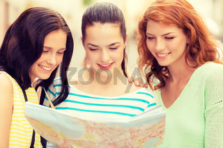 smiling teenage girls with map and camera