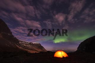 Nordlicht (Auroa borealis) ueber erleuchtetem Zelt, Lappland