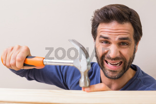 Casual man hammering his finger by accident