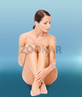 beautiful naked woman touching her legs