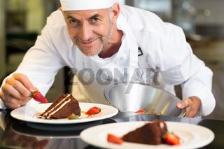 Smiling male pastry chef decorating dessert in kitchen
