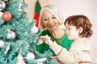 Großmutter und Enkel dekorieren zu Weihnachten Weihnachtsbaum