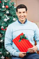 Mann zu Weihnachten mit Geschenk