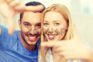 smiling happy couple making frame gesture at home