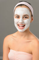 Body care young woman facial mask smiling