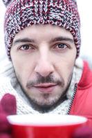Mann mit Teetasse im Winter
