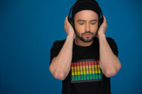 handsome Male DJ with headphones on blue