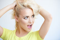 Frustrated blond woman mussing up her long hair