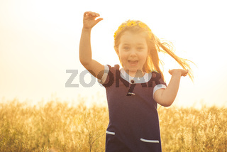 the beautiful little girl in a blue dress laughs